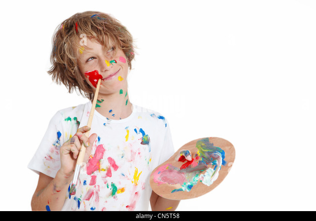 child with paint brush planning mischief - Stock Image