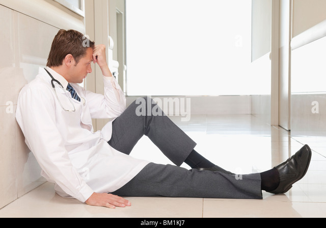 Doctor sitting on the floor looking depressed - Stock Image