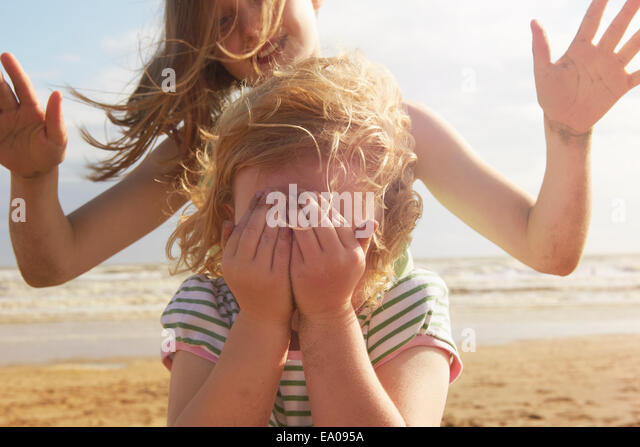 Girl covering eyes in front of sister on beach, Camber Sands, Kent, UK - Stock Image