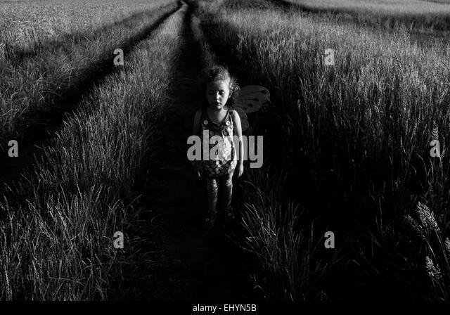 Girl standing in a wheat field - Stock Image