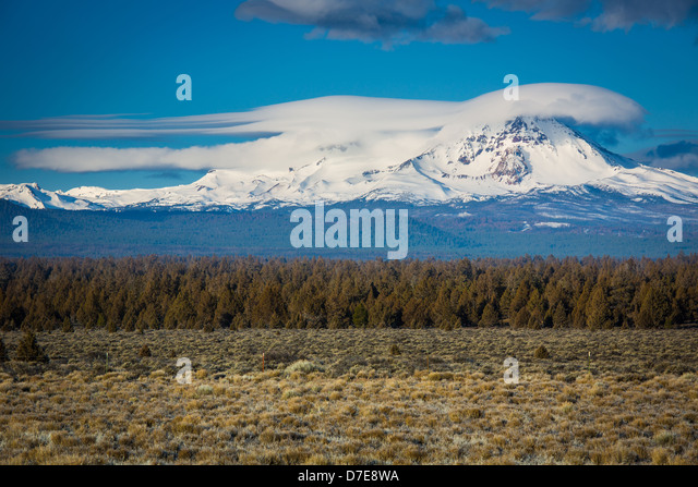 Lenticular clouds hovering over the peak of Broken Top mountains in the Sisters Wilderness of Oregon - Stock Image