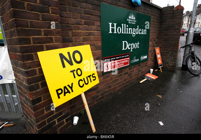A no to pay cuts banner leans against the wall of the Hollingdean Depot in Brighton - Stock Image