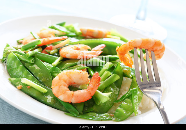 Salt and pepper shrimp with snow peas - Stock Image
