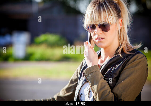 Young woman with sunglasses using mobile phone - Stock-Bilder