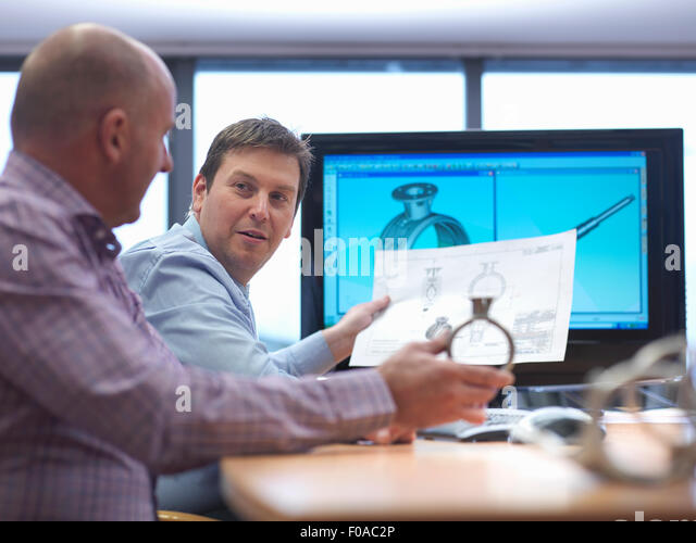 Engineer and client inspecting automotive part at desk - Stock Image