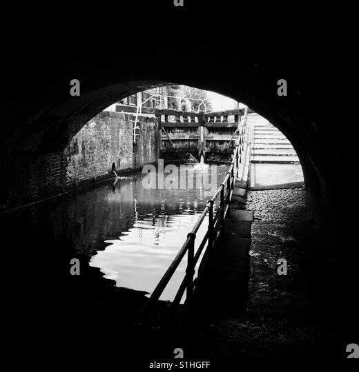 A view of a lock on the Grand Union Canal in Leicester, UK. Taken from underneath a bridge near Frog Island. - Stock Image