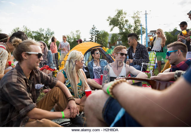Young friends hanging out at summer music festival campsite - Stock Image