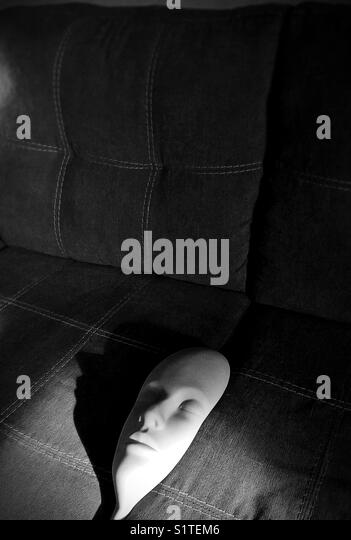 A creepy rubber face coming out of couch cushions. - Stock Image