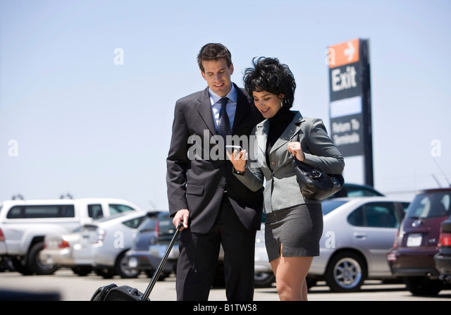 A man and a woman carrying a hand held tracking device in a parking lot. - Stock Image