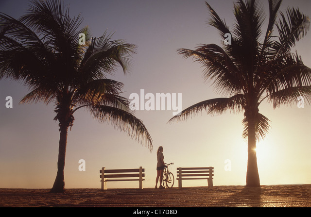 Woman standing with bicycle by palm trees - Stock Image
