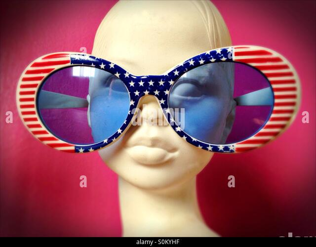 Statuette of a girl wearing American flag glasses. - Stock Image