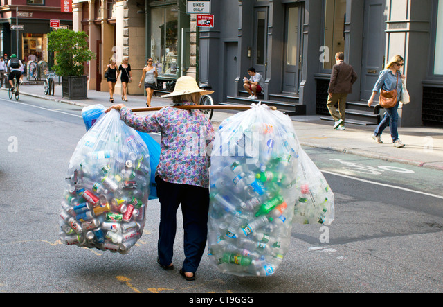 Old Asian woman gathering soda cans and plastic bottles to collect the deposits and recycle Stock Photo
