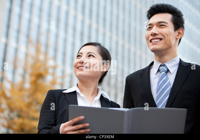 A businessman and businesswoman outside office buildings with a document - Stock Image