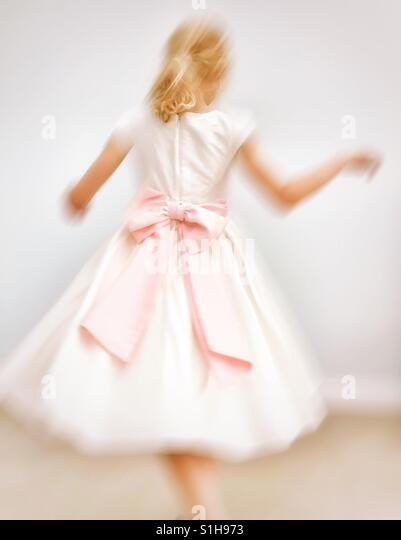Young girl in bridesmaids dress with pink bow twirling round - Stock-Bilder