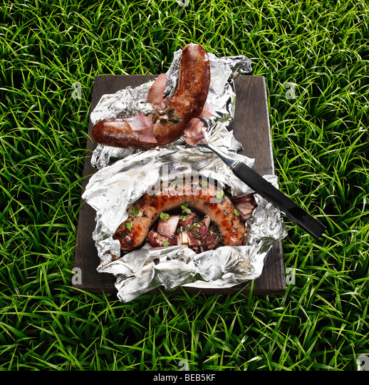 Barbecued sausages on a grass background - Stock Image