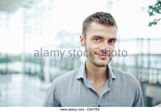 Young man wearing grey shirt, portrait - Stock Image