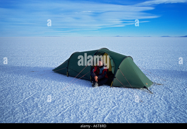 Woman sitting alone in tent with wide expanse of Salar de Uyuni Salt flat around her at 3800 metres altitude in - Stock-Bilder