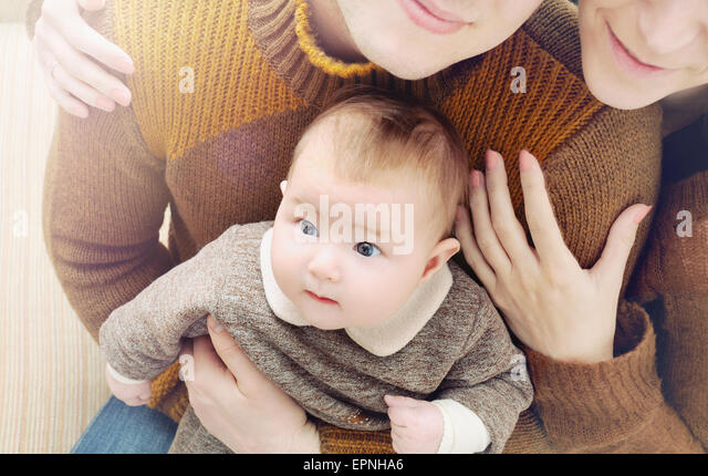 happy family of three, little cute baby with big eyes sitting on the parent's knees, family concept - Stock Image