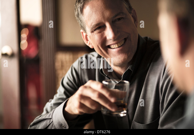 Business colleagues sharing a drink in wine bar - Stock-Bilder