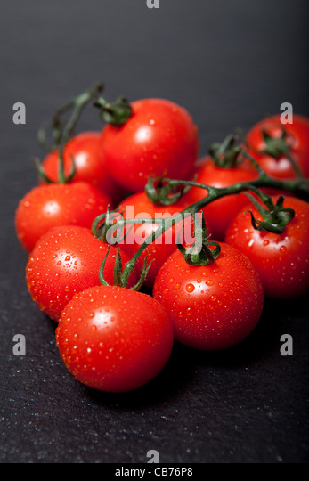 Vine Cherry tomatoes on slate - Stock Image