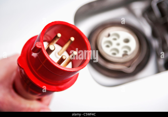 Hand of woman holding high voltage cable near electric car, close up - Stock Image