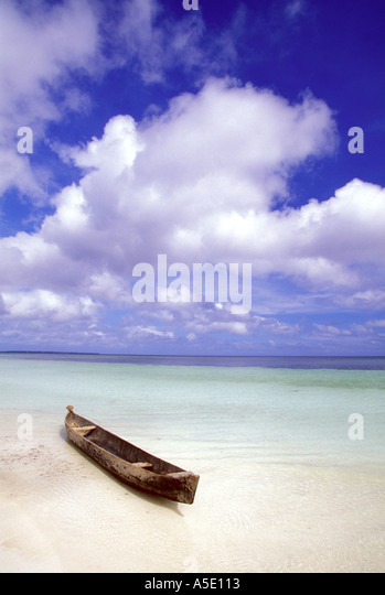 Dugout canoe on white sand beach in the Mallucu Islands of eastern Indonesia - Stock Image