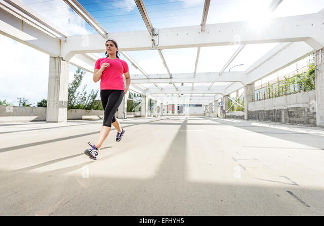 Abstract - Beautiful woman running on a modern metal bridge - Stock-Bilder