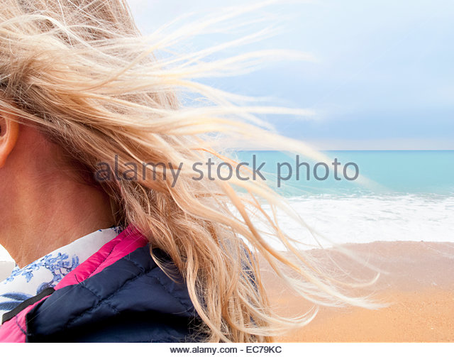 Blond hair blowing in breeze on beach - Stock Image