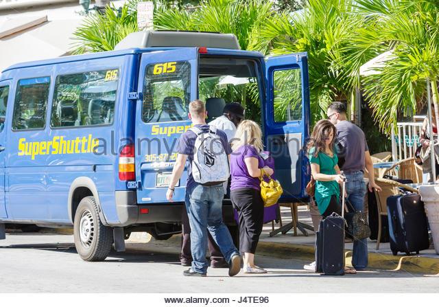 Miami Beach Florida Ocean Drive Super Shuttle van airport ground transportation man woman driver luggage unload - Stock Image