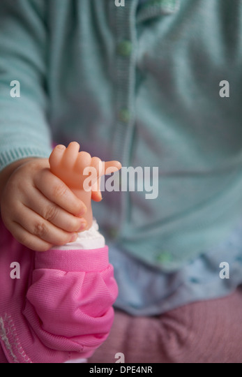 Cropped image of a toddler holding the hand of a toy doll. - Stock Image