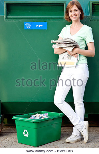 A mid-adult woman recycling paper - Stock Image
