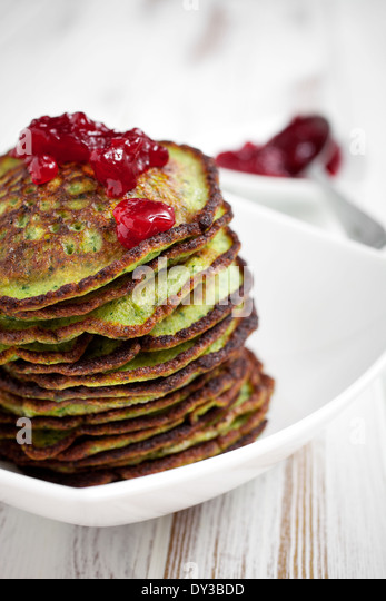 Healthy and delicious spinach pancakes with lingonberry jelly - Stock Image