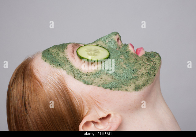 Young woman wearing face mask and cucumber over eyes - Stock Image