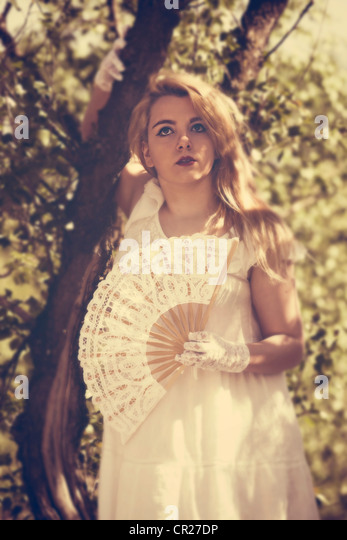 young woman standing in white dress with a fan in the forest - Stock Image
