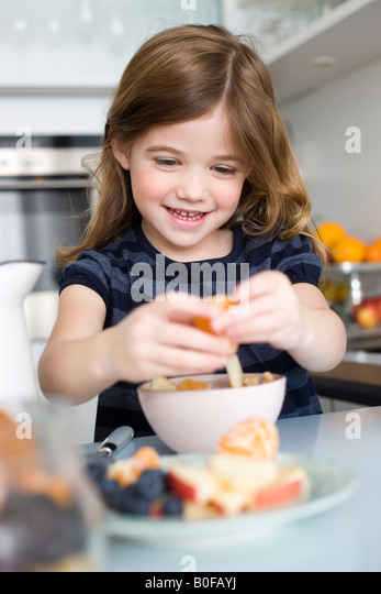 Girls putting fruit into her yogurt - Stock Image