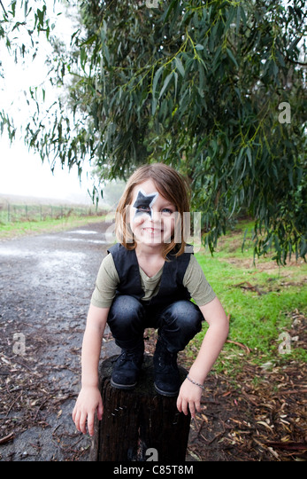 Little boy with face paint perched upon stump - Stock Image