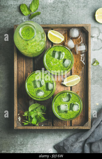 Fresh green smoothie with ice cubes, mint, lime in tray - Stock Image