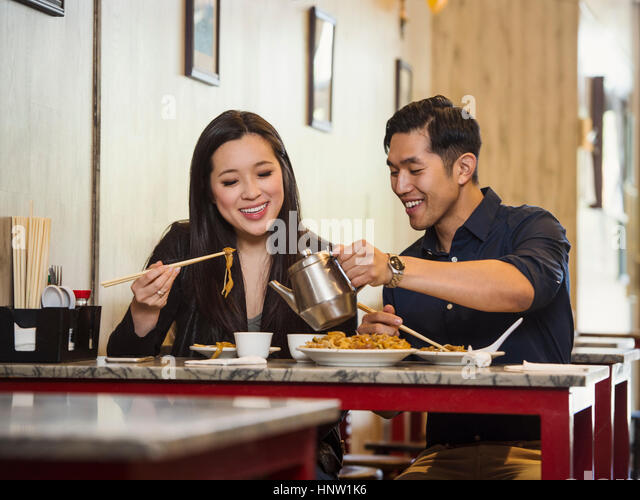 Chinese man pouring tea for woman in restaurant - Stock-Bilder