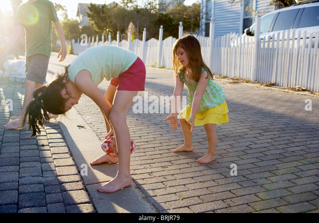 Two little girls are playing football in an alleyway with the sun in background. - Stock Image