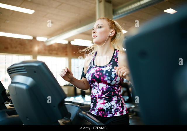 Shot of a woman running on the treadmill at gym. Young focused female working out at health club, training on exercise - Stock Image