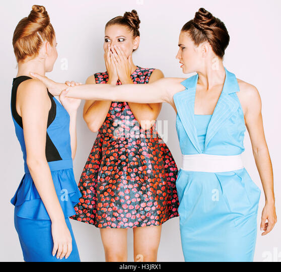 three elegant fashion woman fighting on white background, bright dresses evil faces - Stock Image