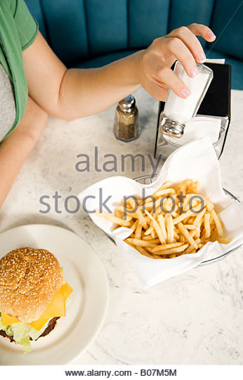 Close up of a girl putting salt on her fries - Stock-Bilder