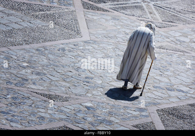 Old Moroccan man in a traditional Djellabah walks in the medina of Chefchaouen, Morocco. - Stock Image