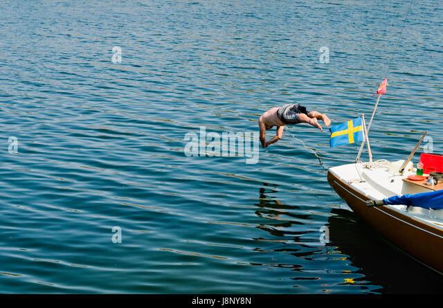 Shirtless man jumping into sea - Stock-Bilder