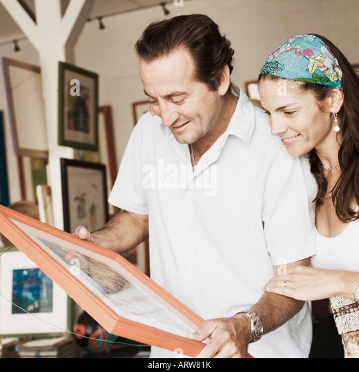 Mid adult couple purchasing paintings from a store - Stock-Bilder
