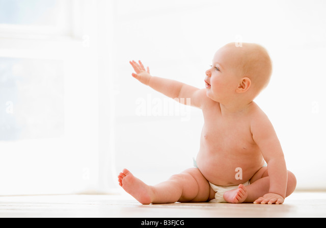 Baby sitting indoors - Stock Image
