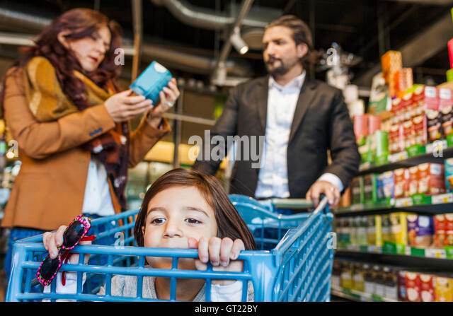 Girl sitting in cart with parents shopping at supermarket - Stock-Bilder