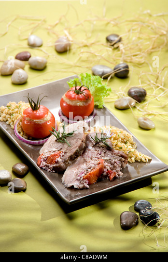 Greek-style shoulder of lamb and steam-cooked tomatoes - Stock Image