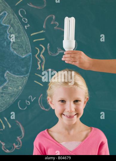 Girl with energy saving lightbulb - Stock Image