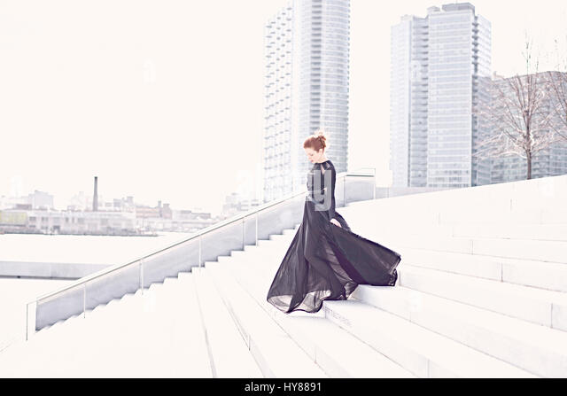 Young women in black gown walking down steps in New York - Stock Image